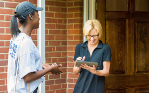 A canvasser interviewing another person at their front door.