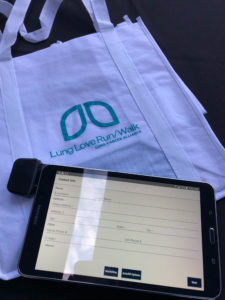 Tote bag that reads Lung Love Run/Walk and has a Grassroots Unwired Android tablet on top of it